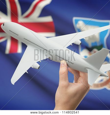 Airplane In Hand With Flag On Background - Falkland Islands