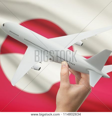 Airplane In Hand With Flag On Background - Greenland