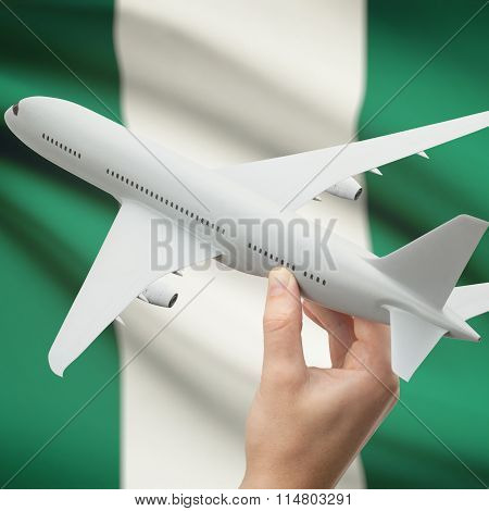 Airplane In Hand With Flag On Background - Nigeria