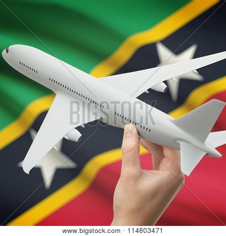 Airplane In Hand With Flag On Background - Saint Kitts And Nevis