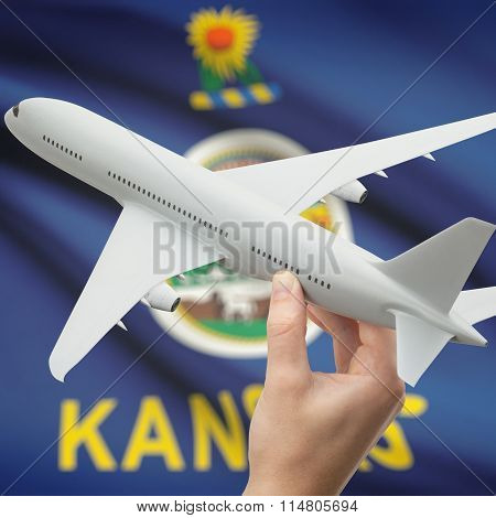 Airplane In Hand With Us State Flag On Background - Kansas