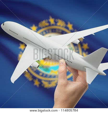 Airplane In Hand With Us State Flag On Background - New Hampshire