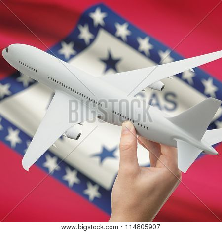 Airplane In Hand With Us State Flag On Background - Arkansas