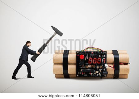 emotional screaming businessman holding big hammer and ready to defusing big bomb with timer over light grey background