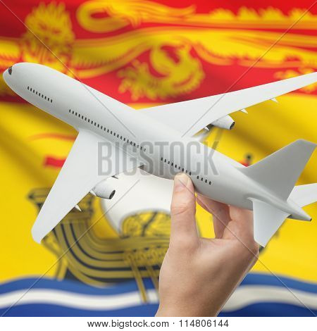 Airplane In Hand With Canadian Province Flag On Background - New Brunswick