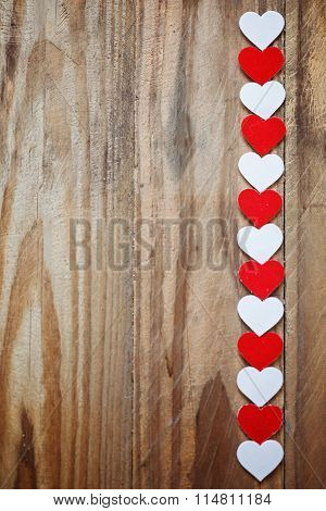 Red And White paper Hearts On The Clothesline On  Wood Background
