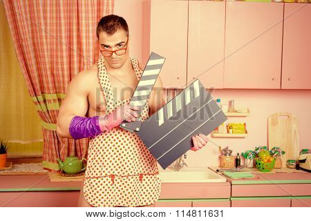 Handsome muscular man in an apron holding clapper board in the pink kitchen. Love concept. Valentine's day. Cinema.
