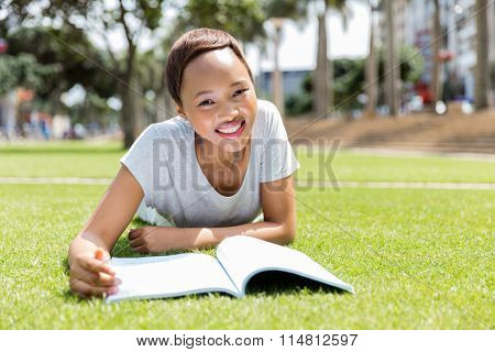 pretty african american college student reading outdoors