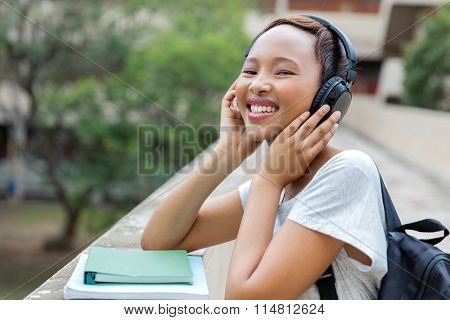cheerful african female university student listening to music on campus