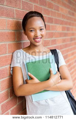 smiling african american female college student leaning against wall