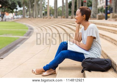 thoughtful african american university student relaxing outdoors