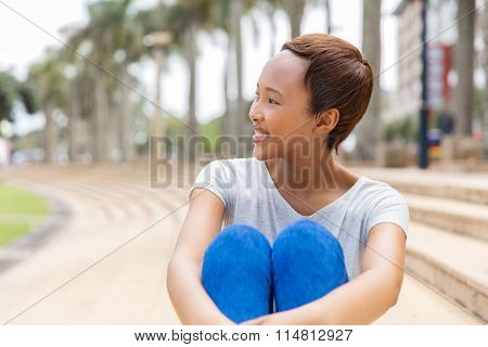 beautiful young african american woman daydreaming outdoors