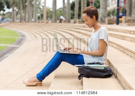 pretty african american girl using laptop outdoors