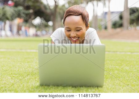 cheerful african college student using laptop outdoors