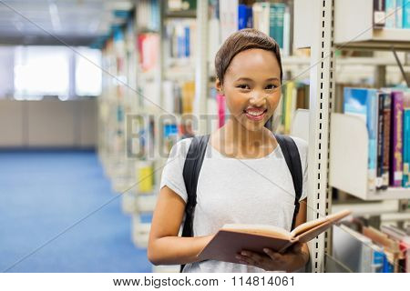 young black college girl reading a book in school library