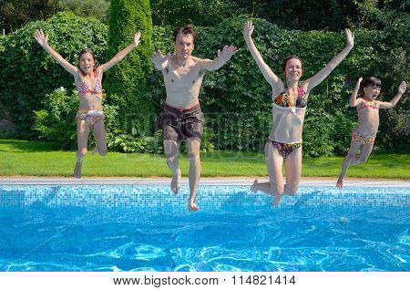Happy family with kids jumping to swimming pool, smiling parents and children having fun on summer
