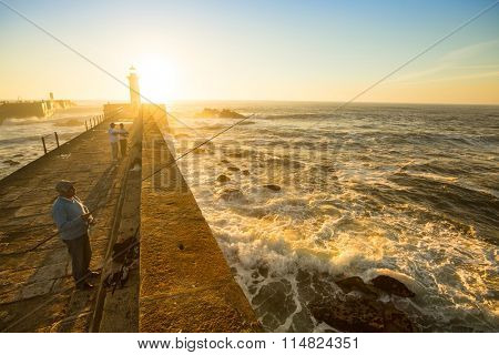 PORTO, PORTUGAL - NOV 7, 2015: Unidentified fishermen on ocean stone pier. In 1996, UNESCO recognised Old Town of Porto as a World Heritage Site.