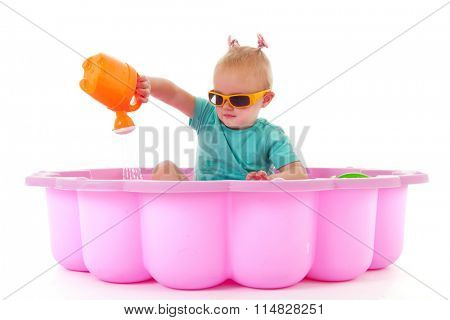 Toddler girl playing in swimming pool isolated over white background