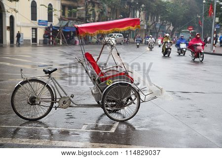 A cyclo waiting for passenger on the side of a street near Sword lake in Hanoi