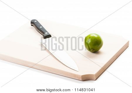 Knife And Lime On Wooden Board.