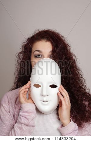 young woman taking off mask