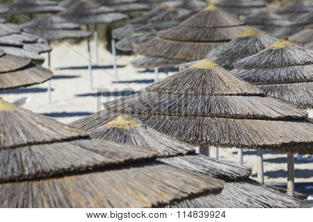 Detail Of Woven Umbrellas Above Rows Of Many Relaxing Beds And Loungers On Beach