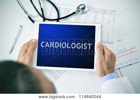closeup of a doctor man sitting at his office desk holding a tablet computer with the word cardiologist in its screen