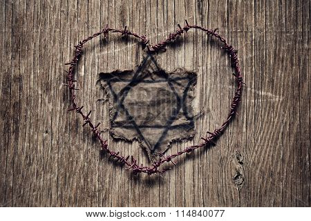 closeup of a Jewish badge and barbed wire forming a heart on a rustic surface, in memory of the victims of the Holocaust