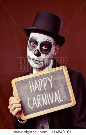 a man with mexican calaveras makeup, wearing jacket, vest, bow tie and top hat, shows a chalkboard with the text happy carnival