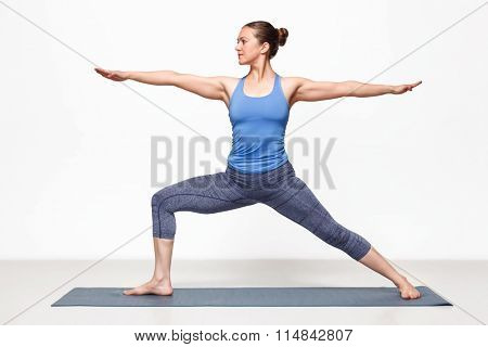 Beautiful sporty fit yogini woman practices yoga asana Virabhadrasana 2 - warrior pose 2