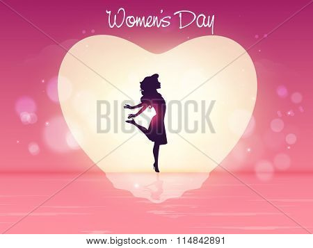 Silhouette of young girl in a heart on shiny creative background for Happy International Women's Day celebration.