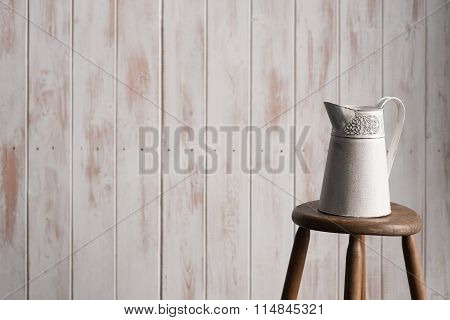 Decorative Pitcher On Stool Over Wooden Backdrop Shot Wide-angle