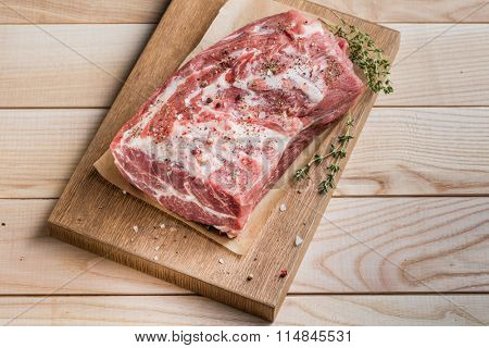 Photo of raw meat. Pork neck with herbs and green thyme on wooden board. Top view