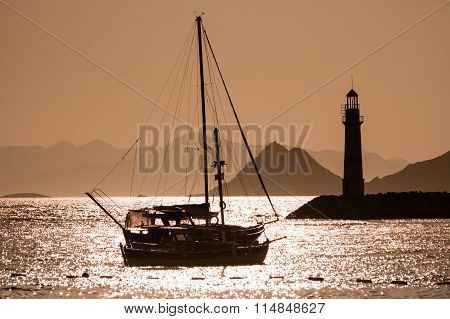 Boats And Lighthouse Silhouette At Sunset