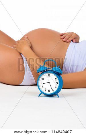 Happy Pregnancy. Pregnant Belly With Alarm Clock. Soon Birth. Fetal Development By Months