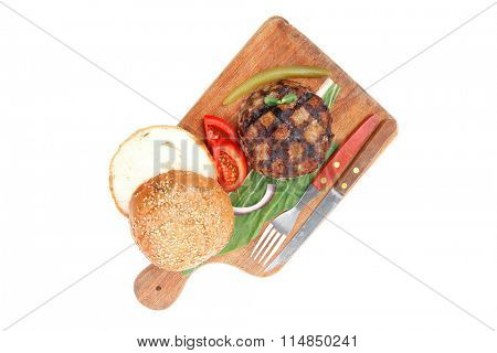 extra thick hot beef meat hamburger lunch on wooden plate with tomatoes and salad isolated on white background