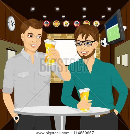 Two cheerful young men talking to each other and gesturing while drinking beer at round table