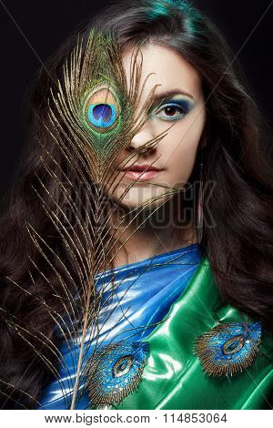 Beauty portrait of beautiful girl covering the eyes with peacock feather. Creative artistic makeup.
