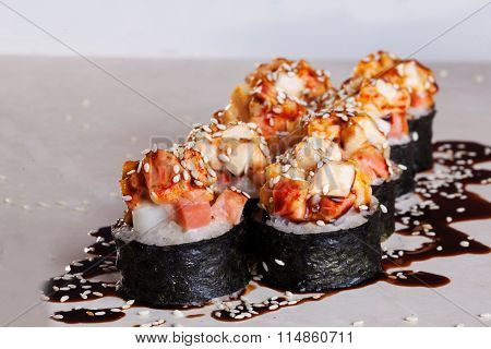 Roll cap salmon and perch, sesame, unagi on a white background isolated close-up menu for sushi orie