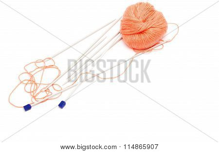 knitting needles and a skein of wool yarn