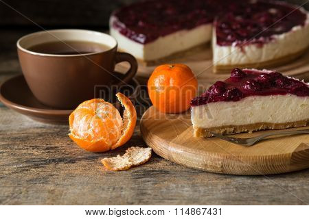 Wedge of classic style cheesecake with cup of tea
