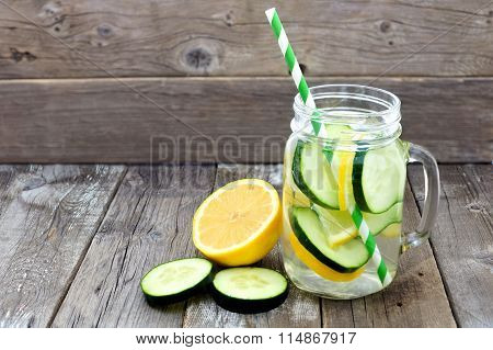 Lemon cucumber detox water in a mason jar against wood