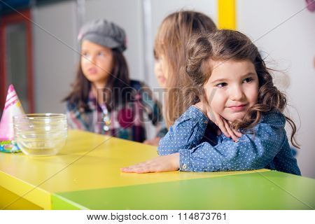 Little girls sitting at the table, waiting for snacks at birthday party