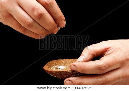 Poor Man Pouring Salt With Dirty Hands On A Piece Of Black Bread