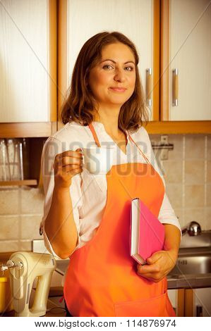 Female Cook Relaxing In Kitchen.