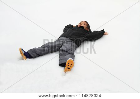 Japanese boy lying on the snow field (4 years old)