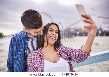 flirty couple taking selfie near santa monica california