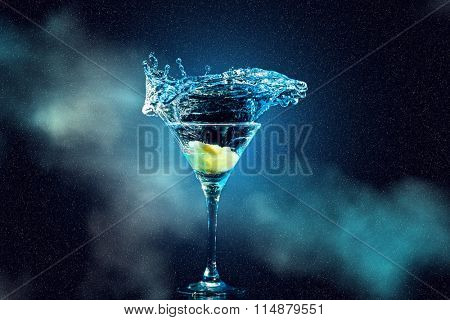 cocktail in glass with splashes and lemon on dark smoky background. Party club entertainment.