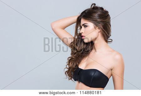 Profile of charming alluring attractive young woman in black bra posing over grey background