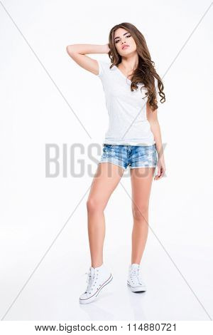Full length of cute lovely young woman with long curly hair in white t-shirt, jeans shorts and sneakers standing over white background